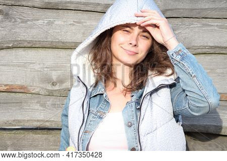Pretty Girl Student Posing Near Wooden Background. Summer Mood. Portrait Of A Caucasian Girl Against