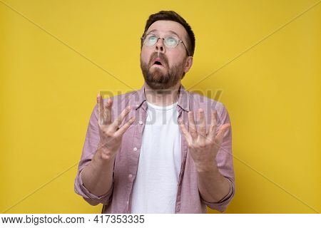 Surprised Man Raised His Hands In Supplication For A Miracle And Puzzled Looks Up.yellow Background.