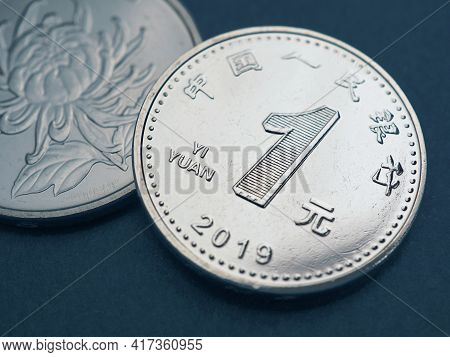 1 Chinese Yuan Coins Lie On A Dark Blue Surface Close-up. Illustration About The Economy, Business,