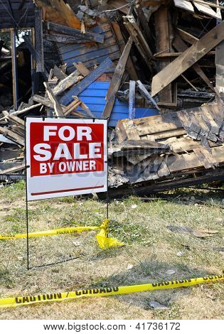Home with fire damage and yellow caution tape and for sale sign