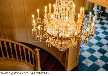 Top View Of An Antique Chandelier. A Huge Crystal Gold Chandelier With Candles, Against The Backdrop