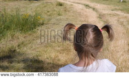 Toddler Girl Head With Rural Landscape Background. Baby Hair Tied With Colorful Rubber Bands In Two