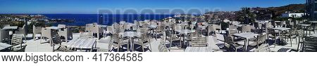Panorama View Of Lots Of Traditional Wooden Tables And Chairs Of A Greek Tavern At Daytime And The V