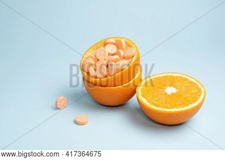 Half Orange And Peel With Vitamin C Tablets On A Blue Background, Close Up. Vitamin C Pills As An Al