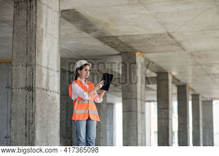 Construction Concept Of Engineer Or Architect Working At Construction Site. A Woman With A Tablet At