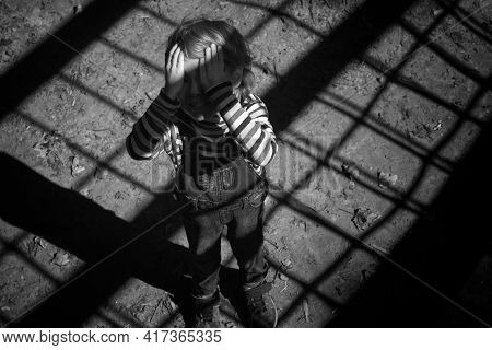 Little Caucasians Blond Boy Child 3-4 Years Old Covered His Face With His Hands Alone In The Dark An