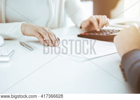 Accountant Checking Financial Statement Or Counting By Calculator Income For Tax Form, Hands Closeup