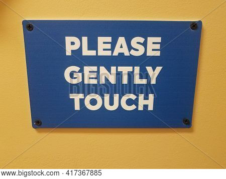 Blue Please Gently Touch Sign On Yellow Wall