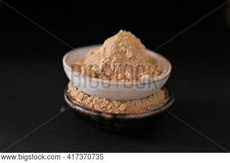 Maca Powder In Ceramic Cups Set On Black Background. Peruvian Ginseng.peruvian Maca Powder Close-up.
