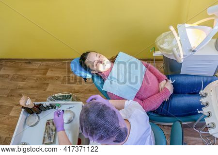 Male Dentists Examining And Working On Young Female Patient.dentists Office. Real Woman In A Chair A