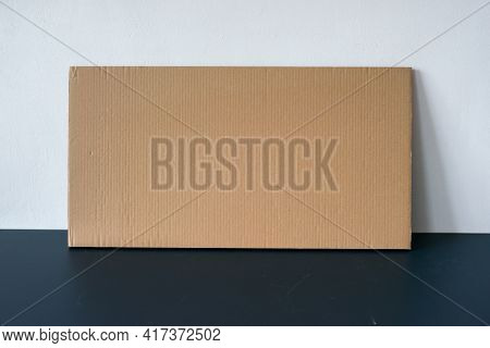 Cardboard Card On The Table By The Wall