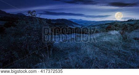 Mountainous Rural Landscape At Night. Beautiful Scenery With Forests, Hills And Meadows In Full Moon