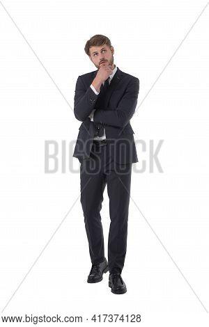Full Length Portrait Of Pensive Business Man Looking Up Holding Hand To Chin Studio Isolated On Whit