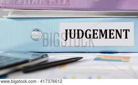 Judgement. Word Written On Folder With Documents And Calculator.