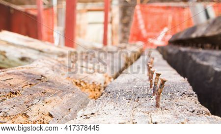 Old Rusty Nails On Wooden Beams On A Construction Site