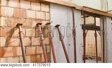 Brick Wall Of A Construction Site With Iron Props And Reinforced Concrete