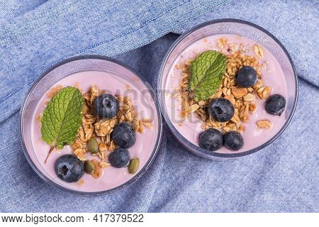 Top View Of Two Glasses Of Strawberry Yogurt With Blueberries And Cereal On A Blue Tablecloth