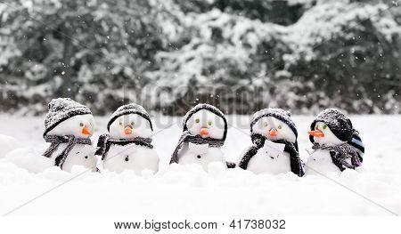 Bonecos de neve pequenos em um grupo