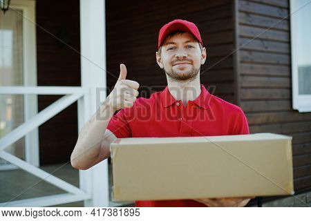 Portrait Of An Handsome Deliverer In Red Uniform Holding A Box. Showing Thumbs Up