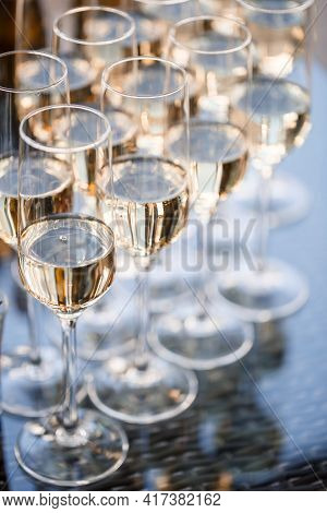 Glass Goblets Filled With Sparkling Champagne And Stand On The Table