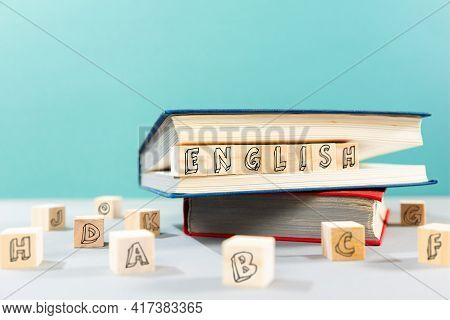 English Language Day. On The Table There Are Books And Wooden Cubes With The Inscription English. Tu