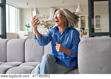 Wow. Big Win. Amused Surprised Mature 60s Aged Woman Over Exited Reacting To Mobile Phone Message Lo