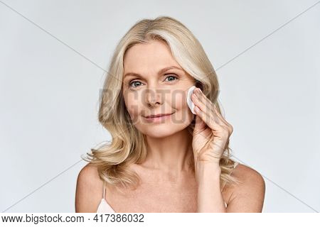 Portrait Isolated On White Of Beautiful Middle Age 50 Woman Doing Her Everyday Routine Removing Her