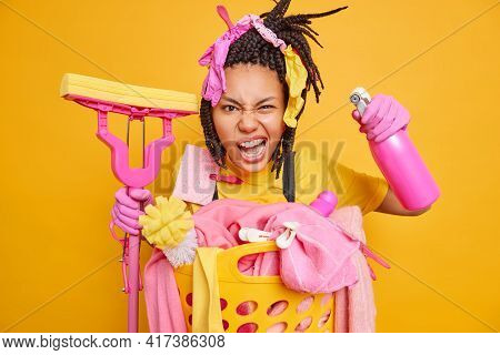 Irritated Adult Woman With Dreadlocks Smirks Face Looks Annoyed Holds Spray Detergent To Disinfect R