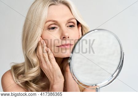 Closeup Portrait Of Gorgeous Happy Middle Age Woman Looking At Mirror Touching Her Skin Enjoying Tre