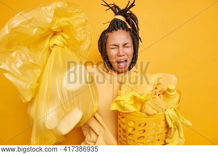 Dejected Frustrated Woman Removes Rubbish And Dirt From House Takes Out Trash Poses With Laundry Bas