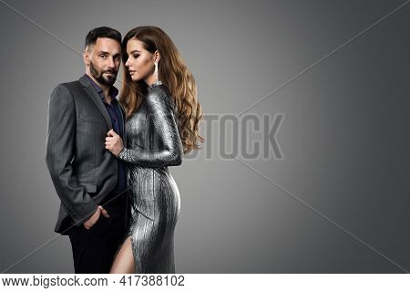 Fashion Couple Man Model Woman. Luxury Glamour Girl In Silver Dress And Elegant Man In Suit. Evening