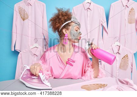 Home And Housekeeping Concept. Curly Haired European Woman Keeps Lips Holds Detergent Spray Busy Doi