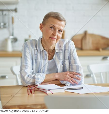 Home Office. Portrait Of Beautiful Middle Aged Woman Smiling At Camera While Sitting At Wooden Table