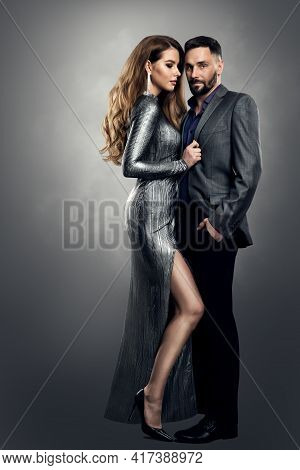 Fashion Woman Man Couple. Luxury Model Girl In Silver Dress Holding Man Elegant Suit. Provocative St