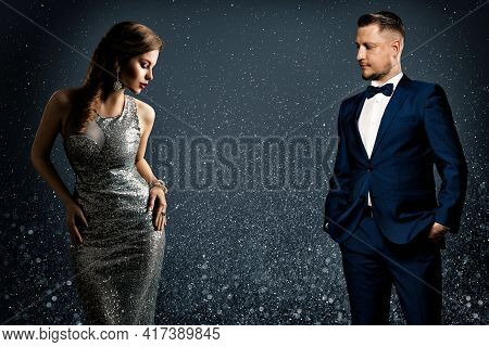 Fashion Luxury Couple. Glamour Woman And Handsome Man. Elegant Pair In Evening Dress And Suit. Spark
