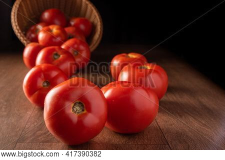 Tomatoes, Beautiful Tomatoes Falling Out Of A Basket On Wooden Surface, Dark Background, Selective F