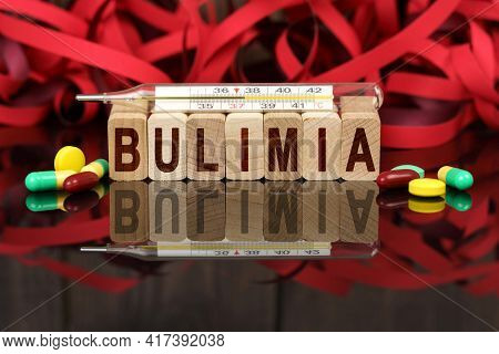 Medicine And Health Concept. On The Surface Are Visible Pills, A Thermometer, Wooden Dies And Their