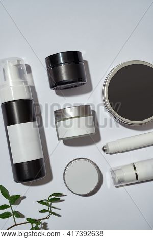 Different Cosmetological Bottles With Blank Labels Lying Beside Green Leaves On White Background, Fl