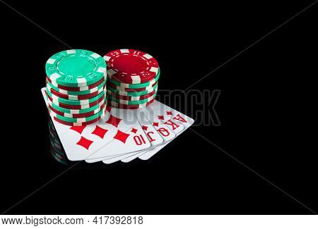 Poker Game With Royal Flush Combination. Chips And Cards On The Black Table. It's A Big Win At Poker