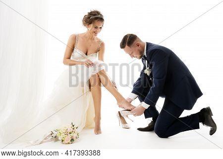 Fashion Wedding Couple. Groom Putting On Cinderella Shoes On Bride Leg. Elegant Bridal Preparation.