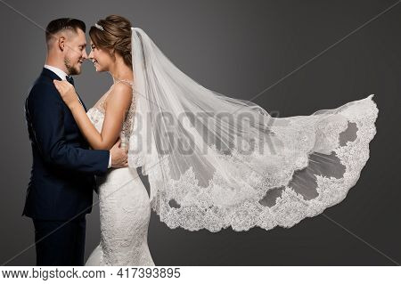 Wedding Couple Dancing. Romantic Bride And Groom Portrait. Bridal Long Veil Flying Over Gray Studio