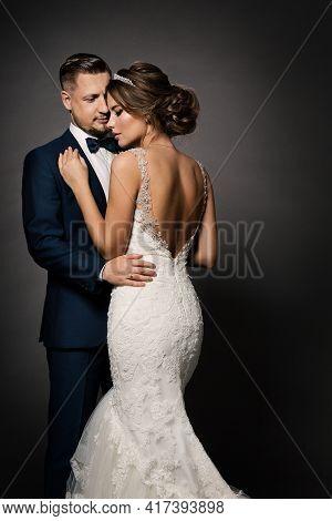 Wedding Couple Fashion Portrait. Bride Back View And Groom Embracing Woman. Black Studio Background