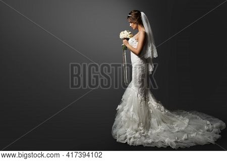 Wedding Dress. Bride In White Gown. Bridal Fashion Model Holding Flower Bouquet. Profile View Over B