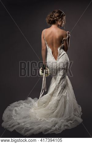 Sexy Bride Back Wedding Dress. Woman Take Off White Gown. Rear View Lady Over Black Background. Brid