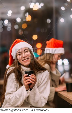 Girl Wearing Santa Hat Sitting In Coffee Shop And Drinking Coffee