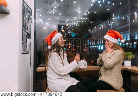 The Girl Gives A Gift To Her Female Friend In Caffe