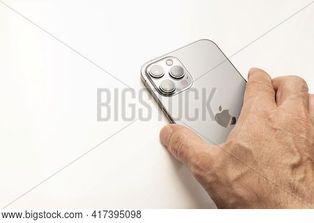 Madrid, Spain - April 18: One Hand Holding The New Iphone 12 Pro Max Seen From The Back, On A White