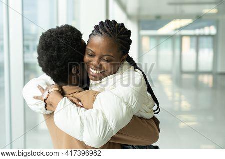 Couple Reunion In Airport: Portrait Of Happy African American Female Met Hug Boyfriend Arriving From