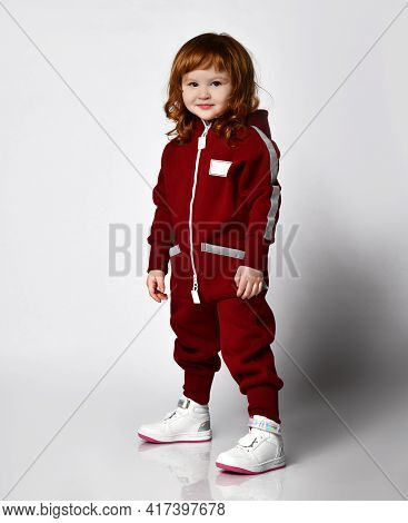 Little Red-haired Preschooler Girl Wearing Warm Tracksuit Sportswear With Hood And White Sneakers. S
