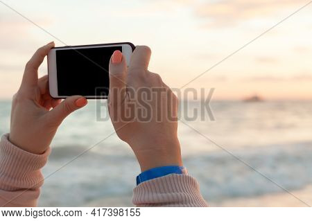 Woman Holds Smart Phone In Hands For Taking Outdoor Photo On A Summer Morning, Beach In Dominican Re